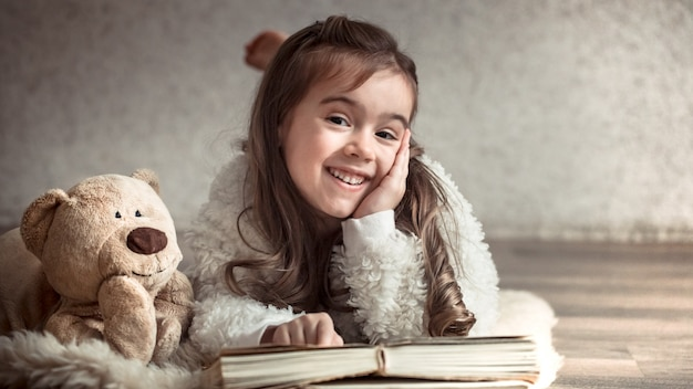 Petite fille lisant un livre avec un ours en peluche sur le sol, concept de détente et d'amitié