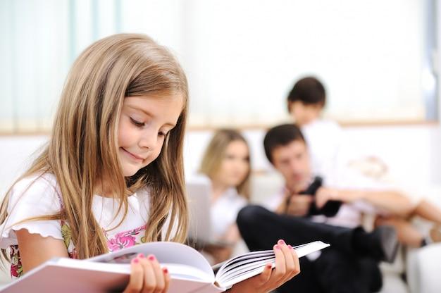 Petite fille lisant à la maison, à l'intérieur avec une famille heureuse