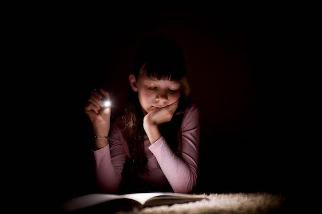 Petite fille lit un livre avec une lampe de poche dans une pièce sombre la nuit.