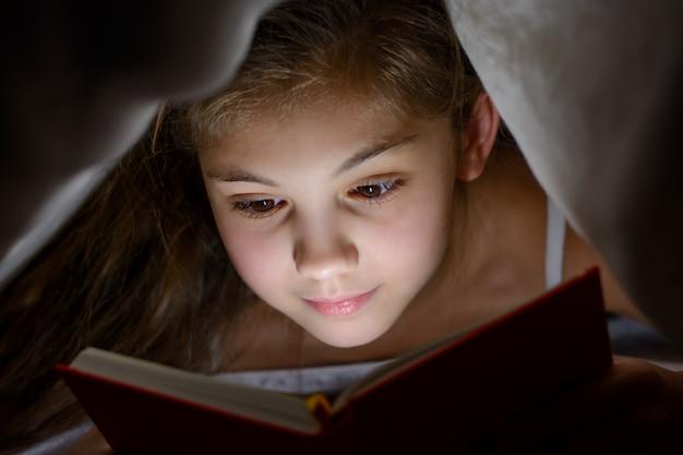 Petite fille lit un livre avec une lampe de poche sous la couverture au lit