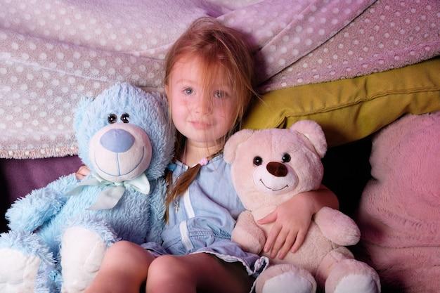 Petite fille sur le lit à la maison avec des ours en peluche jouets préférés, le concept d'une enfance heureuse.