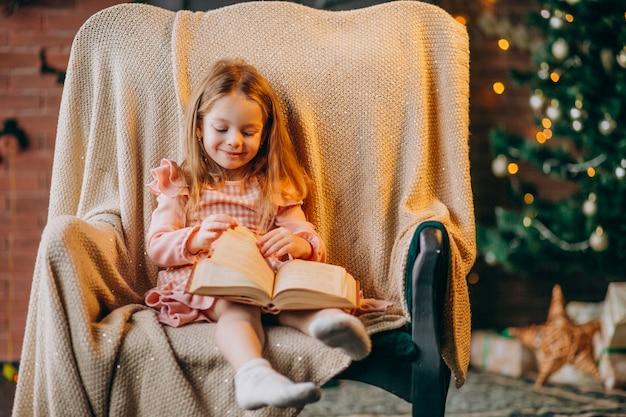 Petite fille avec un livre assis sur une chaise près d'un arbre de noël