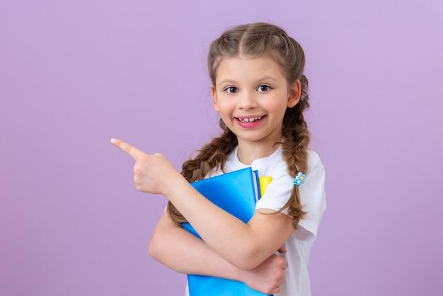 Une petite fille avec un livre pointe son doigt sur le côté.