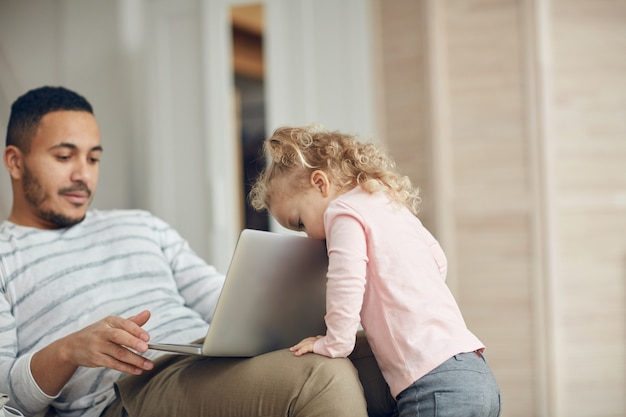 Petite fille lorgnant à papas ordinateur portable