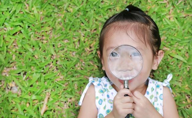 Petite fille avec une loupe
