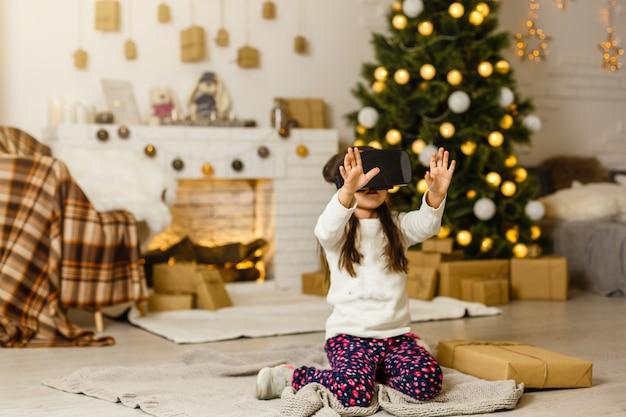 Petite fille avec des lunettes 3d virtuelles à noël à la maison