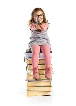 Petite fille avec des lunettes assis sur des livres. retour à l'école