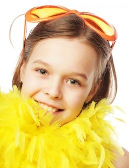 Petite fille avec des lunettes de carnaval orange amusantes