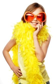 Petite fille avec des lunettes de carnaval orange drôles