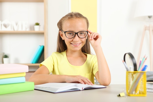Petite fille avec des lunettes lisant un livre à la maison