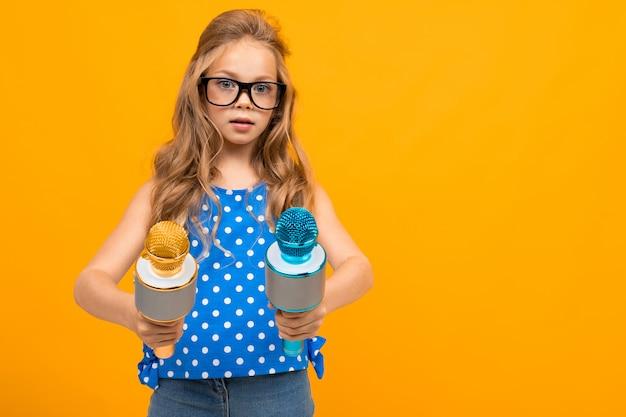 Une petite fille à lunettes avec un microphone est interviewée, la photo est isolée sur fond jaune