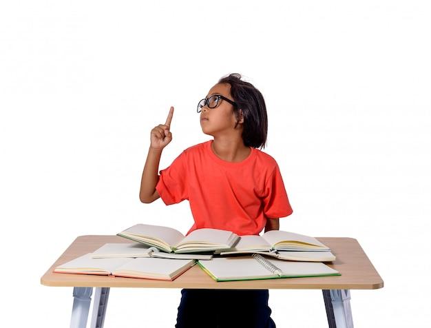 Petite fille à lunettes pensée et beaucoup de livre sur la table. concept de retour à l'école
