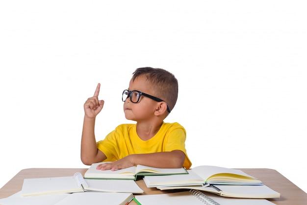 Petite fille à lunettes pensée et beaucoup de livre sur la table.