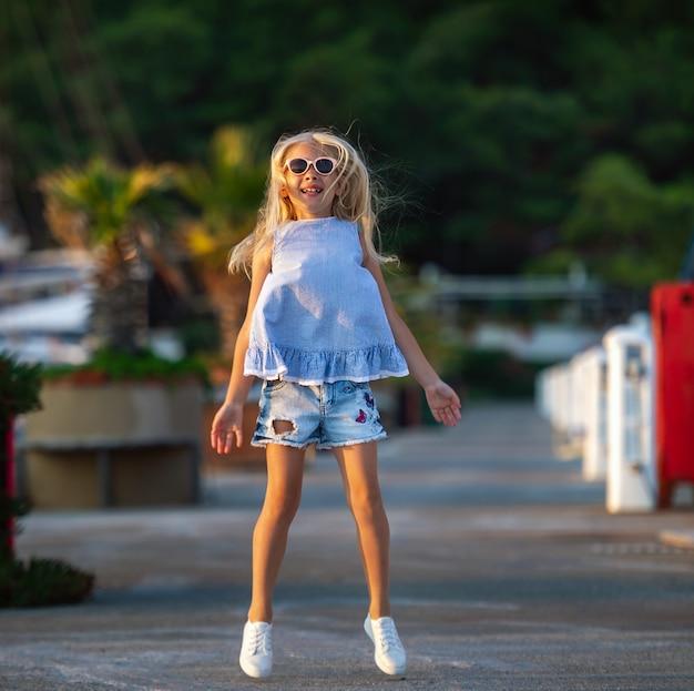 Une petite fille avec des lunettes rebondit sur la jetée.une fille en short et un t-shirt bleu s'amuse.turquie