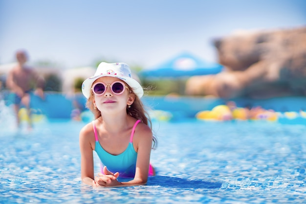 Petite fille à lunettes de soleil et chapeau avec licorne dans la piscine extérieure du complexe de luxe en vacances d'été sur l'île tropicale
