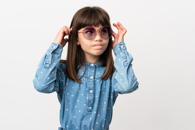 Petite fille avec des lunettes de soleil isolé sur fond blanc ayant des doutes et de la pensée
