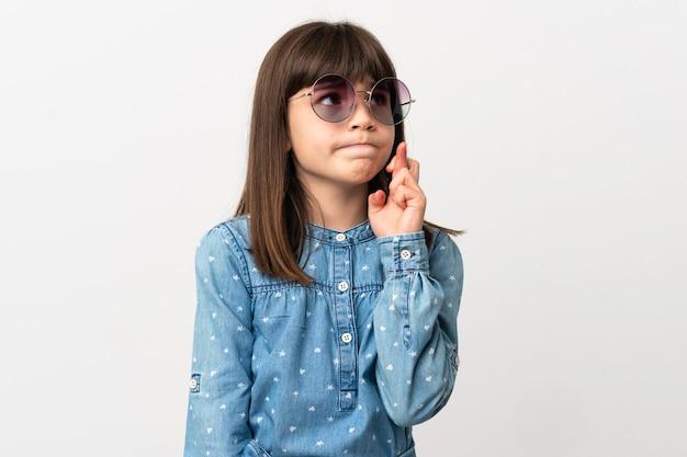 Petite fille avec des lunettes de soleil isolé sur fond blanc avec les doigts qui se croisent et souhaitant le meilleur