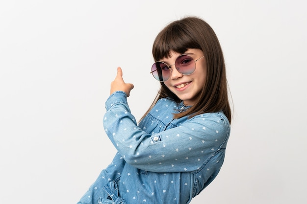 Petite fille avec des lunettes de soleil isolé sur fond blanc pointant vers l'arrière