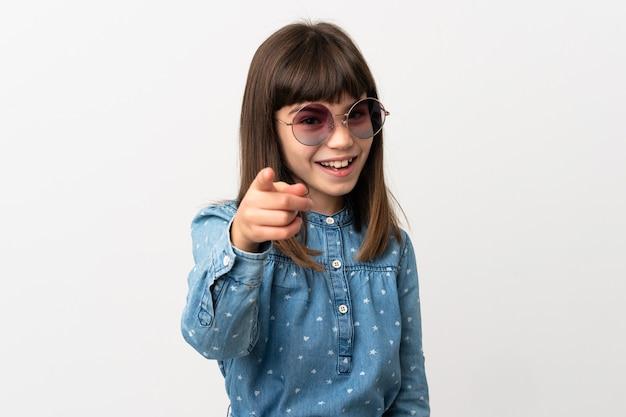 Petite fille avec des lunettes de soleil isolé sur fond blanc surpris et pointant vers l'avant