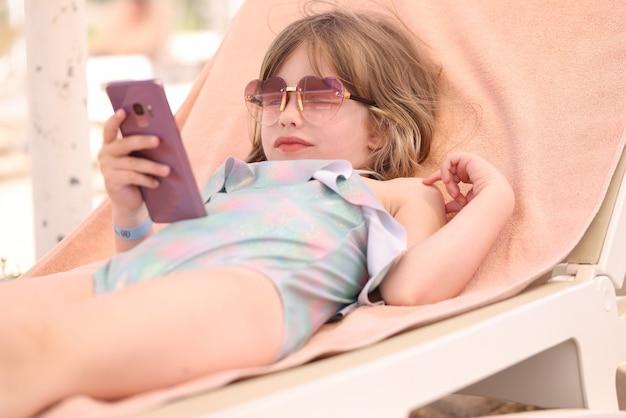 Petite fille à lunettes de soleil et maillot de bain allongée sur une chaise longue avec un téléphone portable dans les mains