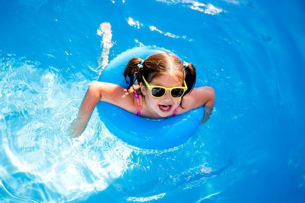Petite fille à lunettes de soleil nage sur une bouée de sauvetage