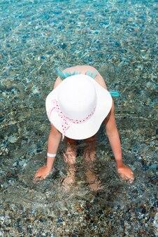 Petite fille en maillot de bain et chapeau blanc à la mer. vacances d'été en mer egée, île de kos, grèce