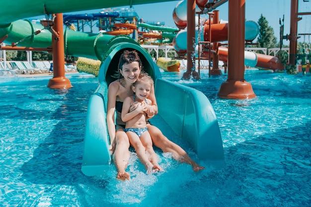 Petite fille en maillot de bain descend les toboggans bleus à la piscine maman et fille jouent et nagent dans la piscine extérieure