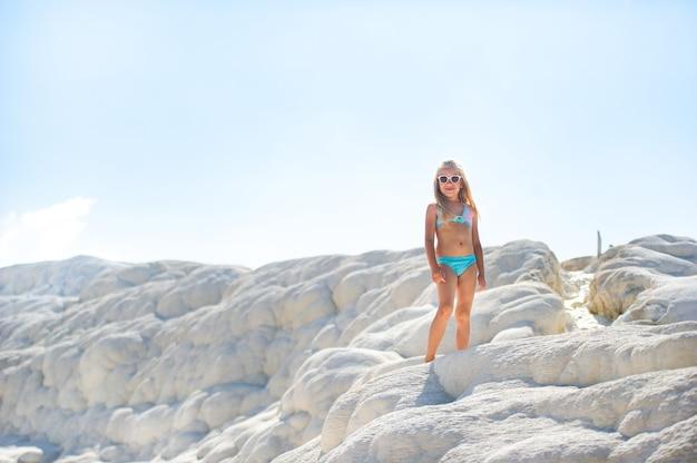 Une petite fille en maillot de bain et lunettes de soleil sur la montagne de sel blanc à pamukkale .turquie