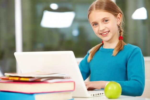 Petite fille avec le maillot bleu étudiant avec un ordinateur portable