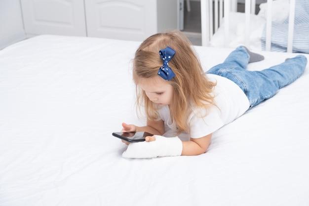 Petite fille avec la main en plâtre portant dans son lit à l'aide de smartphone, regardant une vidéo de dessin animé ou d'éducation.