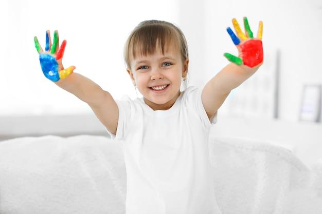 Petite fille avec les mains dans la peinture, sur la surface intérieure de la maison