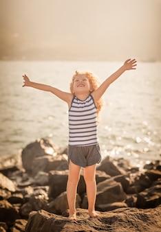 Petite fille avec les mains levées sur un rocher près d'une mer