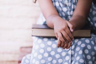 Petite fille les mains sur un livre. tonalité de couleur vintage