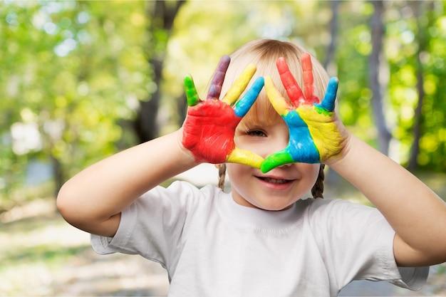 Petite fille avec les mains en peinture sur fond