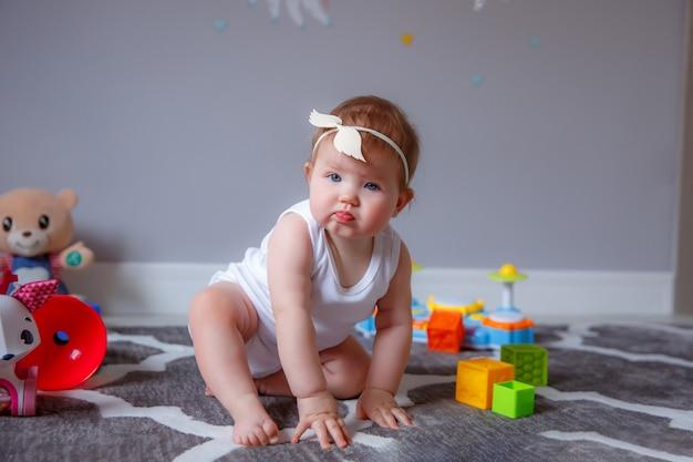 Petite fille à la maison assis sur le sol jouant avec des jouets