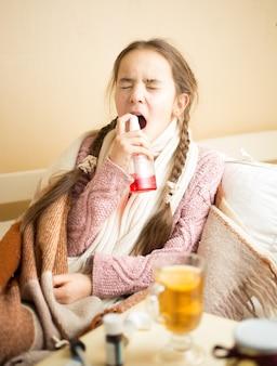 Petite fille malade allongée dans son lit et utilisant un spray pour la gorge