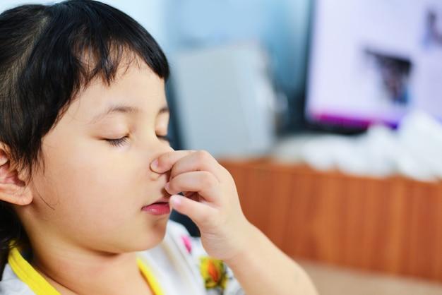 Petite fille malade avec une main tenant son nez
