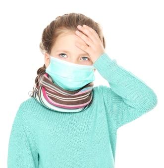 Petite fille malade en masque facial sur fond blanc