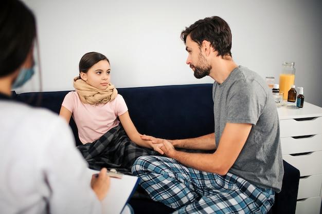Petite fille malade s'asseoir sur le canapé. sa gorge est couverte d'un foulard. couverture allongée sur les jambes. son père lui tient la main et sourit. il s'assoit d'ailleurs. femme médecin écrit la prescription de médicaments.