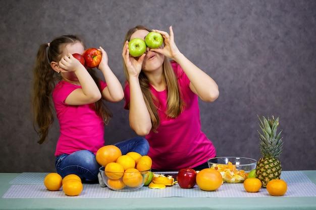 Petite fille avec maman joue avec des fruits et souriante. vitamines et alimentation saine pour les enfants.