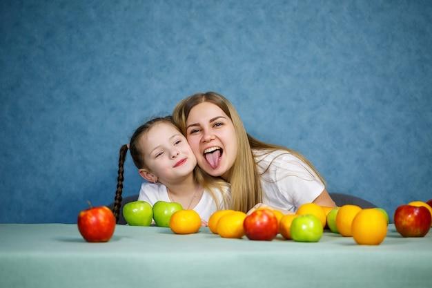 Petite fille et maman jouent avec des fruits et s'amusent. ils portent des tee-shirts
