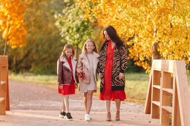 Petite fille avec maman en plein air dans le parc au jour de l'automne