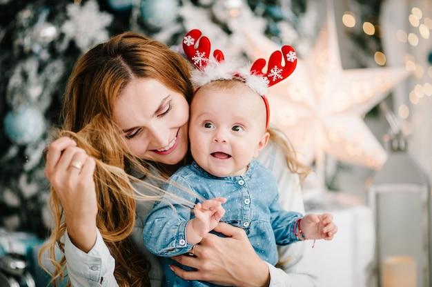 Petite fille avec maman sur le sol près de l'arbre de noël. joyeux noël. intérieur décoré de noël. le concept de vacances en famille.