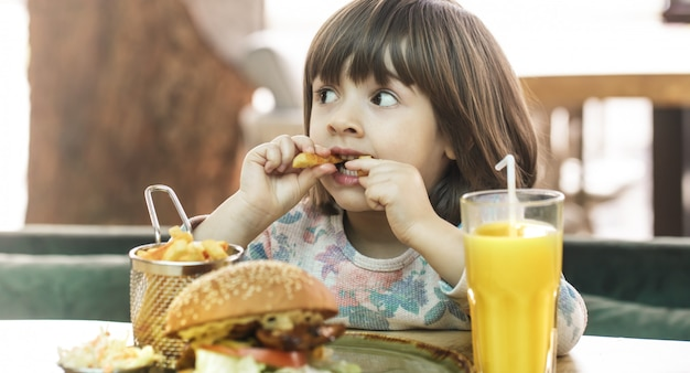 Petite fille mange dans un café de restauration rapide