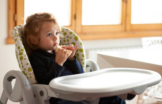 Petite fille mange du pain dans la chaise haute