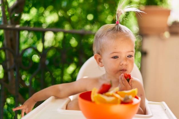 La petite fille mange des fraises perdues dans ses pensées