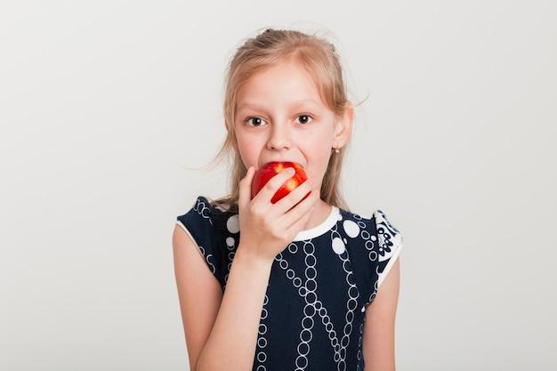 Petite fille mange une pomme