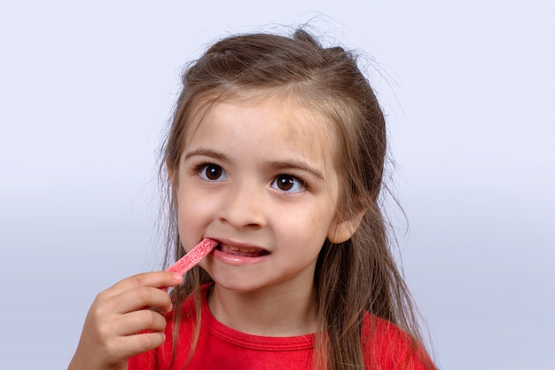 Petite fille mangeant des bonbons sucrés.
