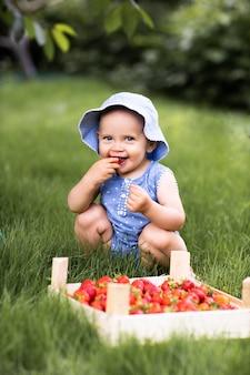Petite fille mangeant des fraises dans la nature