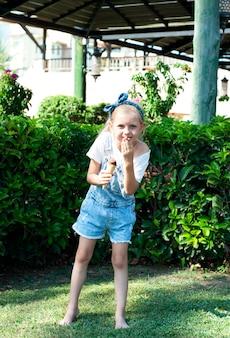 Petite fille mangeant de la glace au chocolat à l'extérieur